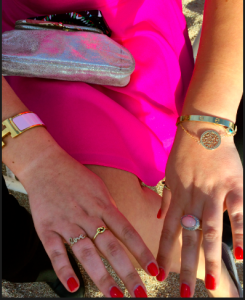 A Cartier 18kt gold Love Bracelet on one arm, & her 14kt Sydney Evans Love Ring on the other hand.