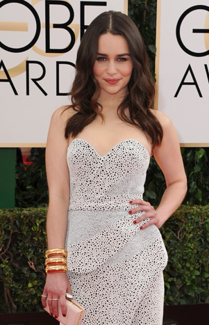 Emilia Clarke from Game of Thrones, chose jewels that her on-screen warrior princess would approve of, stacked statement yellow gold bangles and feather earrings by Sidney Garber.